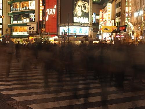 夜の渋谷スクランブル交差点を渡る人達